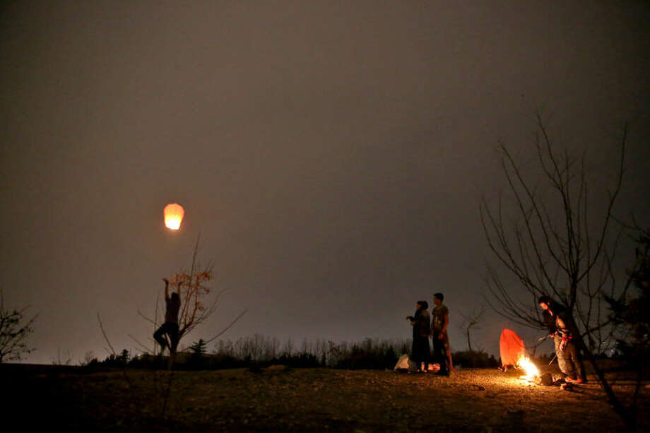 An Iranian man flies a wishing lantern in the Pardisan Park in Tehran, Iran, Tuesday, March 18, 2014, during Chaharshanbe Souri, or Wednesday Feast, an ancient Festival of Fire, on the eve of the last Wednesday of the year, when Iranians jump over burning bonfires and throw firecrackers celebrating arrival of the spring which coincides with their new year, or Nowruz, which begins on March 21. (AP Photo/Ebrahim Noroozi)