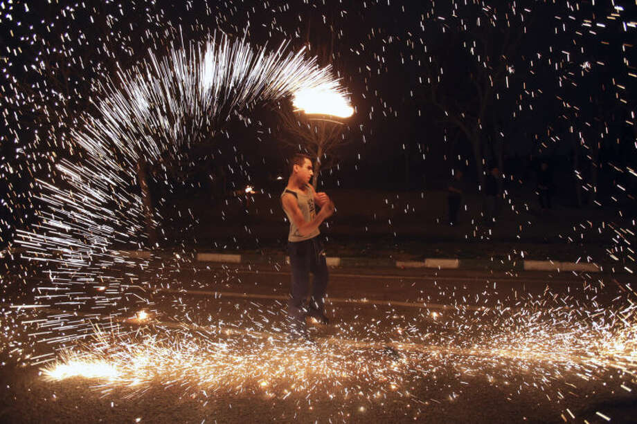 An Iranian man plays with a firework in the Pardisan Park in Tehran, Iran, Tuesday, March 18, 2014, during Chaharshanbe Souri, or Wednesday Feast, an ancient Festival of Fire, on the eve of the last Wednesday of the year, when Iranians jump over burning bonfires and throw firecrackers celebrating arrival of the spring which coincides with their new year, or Nowruz.