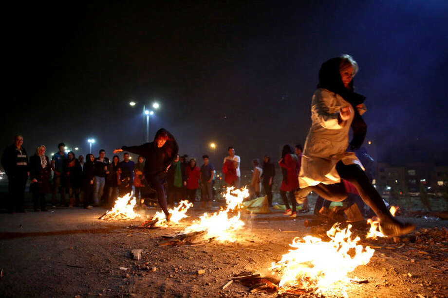 Two Iranian women jump over bonfires in the Pardisan Park in Tehran, Iran, Tuesday, March 18, 2014, during Chaharshanbe Souri, or Wednesday Feast, an ancient Festival of Fire, on the eve of the last Wednesday of the year, when Iranians jump over burning bonfires and throw firecrackers celebrating arrival of the spring which coincides with their new year, or Nowruz, which begins on March 21. (AP Photo/Ebrahim Noroozi)