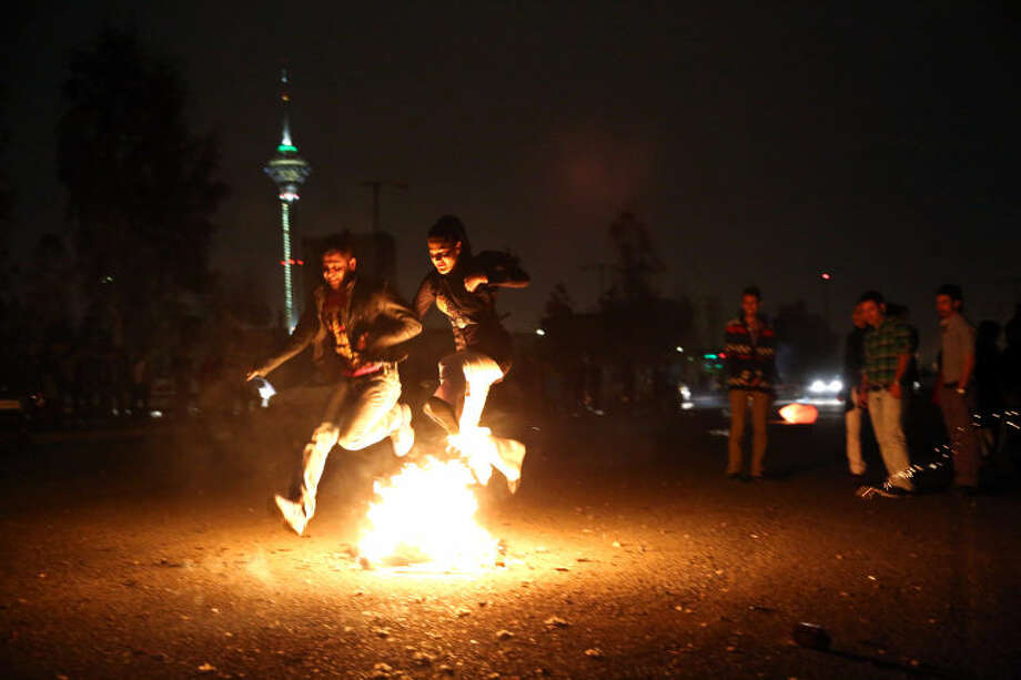 Two Iranians jump over a bonfire in the Pardisan Park in Tehran, Iran, Tuesday, March 18, 2014, during Chaharshanbe Souri, or Wednesday Feast, an ancient Festival of Fire, on the eve of the last Wednesday of the year, when Iranians jump over burning bonfires and throw firecrackers celebrating arrival of the spring which coincides with their new year, or Nowruz, which begins on March 21. (AP Photo/Ebrahim Noroozi)