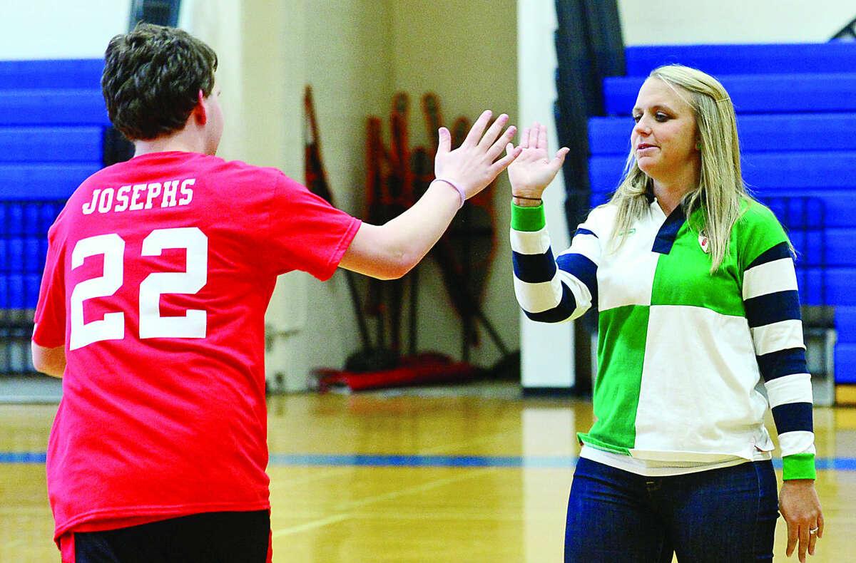 Head coach Kelsey Murphy congratulates Matthew Josephs during Brien McMahon High School's new Unified Sports Team practice on Tuesday. (Hour photo / Erik Trautmann)