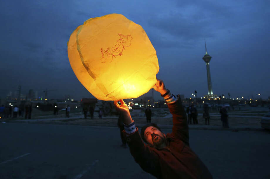 "In this picture taken on Tuesday, March 18, 2014, an Iranian man releases a lit lantern during a celebration, known as ""Chaharshanbe Souri,"" or Wednesday Feast, marking the eve of the last Wednesday of the solar Persian year, in Pardisan park, Tehran, Iran. The festival has been frowned upon by hard-liners since the 1979 Islamic revolution because they consider it a symbol of Zoroastrianism, one of Iran's ancient religions of Iranians. They say it goes against Islamic traditions. (AP Photo/Vahid Salemi)"