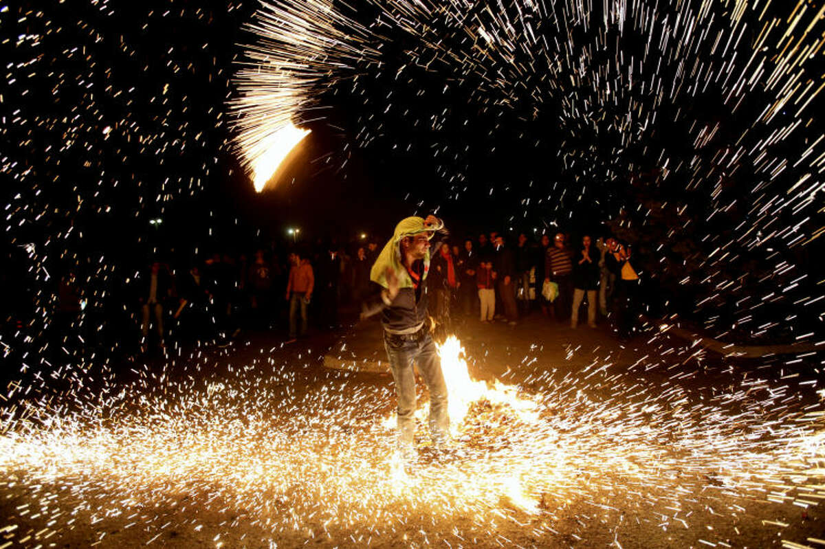 In this picture taken on Tuesday, March 18, 2014, an Iranian man lights fireworks during a celebration, known as