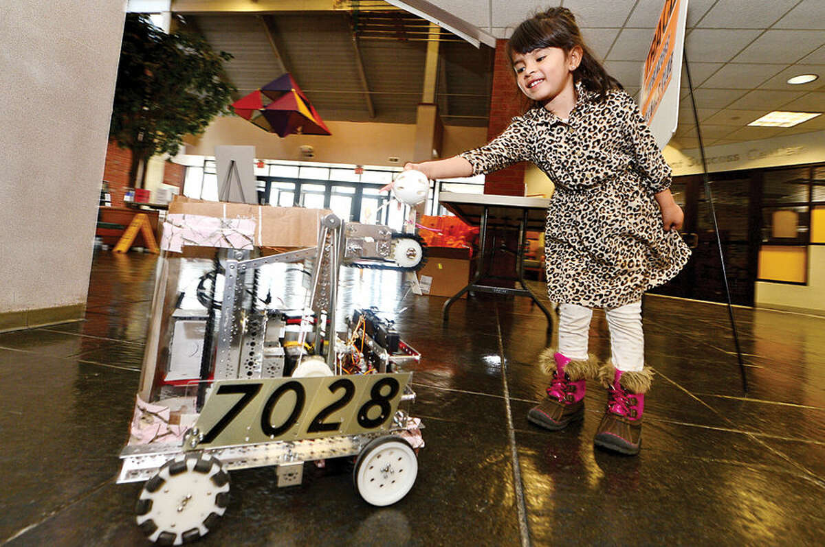 Hour photo / Erik Trautmann 4 year old Chelsea Sanchex greets a robot developed by the Flaming Marshmellows robotics team as the Norwalk Community College Extended Studies Division hosts The Amazing Girl Science Conference: Amusement Park Physics event for girls grades 4 to 8 Saturday at the college's East Campus. The Amusement Park Experience, part of the Saturday Academy for Girls, and the NCC College for Kids Program, provided students an opportunity to combine real-world applications with STEM concepts.