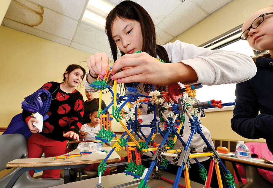 Hour photo / Erik Trautmann Caoillainn Bischoff puts the finishing touches on her K'Nex amusement park ride as the Norwalk Community College Extended Studies Division hosts The Amazing Girl Science Conference: Amusement Park Physics event for girls grades 4 to 8 Saturday at the college's East Campus. The Amusement Park Experience, part of the Saturday Academy for Girls, and the NCC College for Kids Program, provided students an opportunity to combine real-world applications with STEM concepts.
