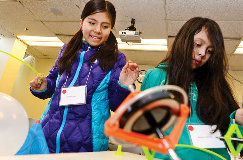 Hour photo / Erik Trautmann Brenda Ames and Stephanie Astuchillo conduct a centripetal force experiment as the Norwalk Community College Extended Studies Division hosts The Amazing Girl Science Conference: Amusement Park Physics event for girls grades 4 to 8 Saturday at the college's East Campus. The Amusement Park Experience, part of the Saturday Academy for Girls, and the NCC College for Kids Program, provided students an opportunity to combine real-world applications with STEM concepts.