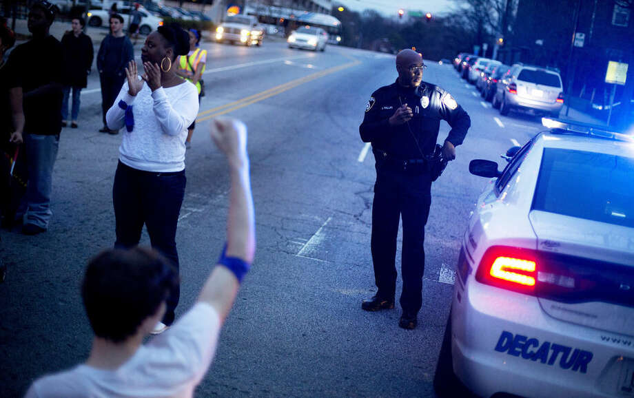 FILE - In this March 11, 2015. file photo, a police officer stands watch while standing at an intersection during a protest against the shooting death of Anthony Hill by a police officer, in Decatur, Ga. The police shooting in Georgia earlier this month of a naked, unarmed black man with bipolar disorder spotlights the growing number of violent confrontations between police and the mentally ill _ an issue that goes before the Supreme Court this week. (AP Photo/David Goldman)