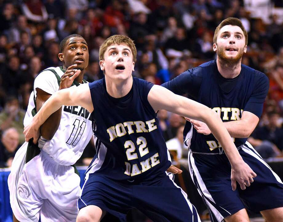 Hour photo/John Nash - Notre Dame-Fairfield's Colin Burke (22), a resident of Norwalk, boxes out during Notre Dame-Fairfield's Class M championship game against Weaver at the Mohegan Sun Arena on Saturday.
