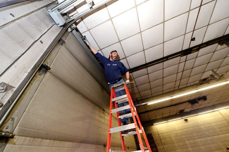 Hour photo / Erik Trautmann John Mathew Vella of New England Overhead Door makes repairs to the bay doors at Norwalk Fire Department's Brad River station. Norwalk Fire Department to renovate Broad River Station No. 1 at 90 New Canaan Ave. later this year. Reallocation of $934,000 leftover from new headquarters construction will pay for the work.