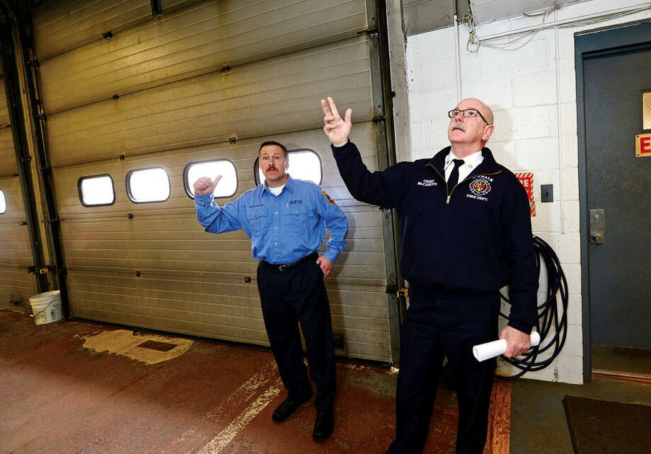 Hour photo / Erik Trautmann Norwalk Fire Chief Denis McCarthy and Captain Michel McCallum point out what improvements will be made in renovations to Broad River Station No. 1 at 90 New Canaan Ave. later this year during a tour of the fire station Friday. Reallocation of $934,000 leftover from new headquarters construction will pay for the work.