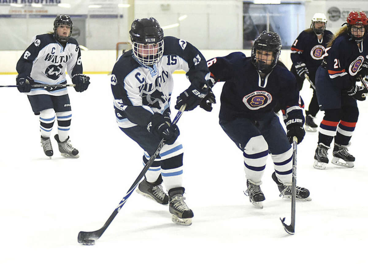 Wilton's Elizabeth Craven (15) plays the puck against the defense of Stamford-Westhill-Staples' Mary Leydon during Tuesday's game at the SoNo Ice House in Norwalk.