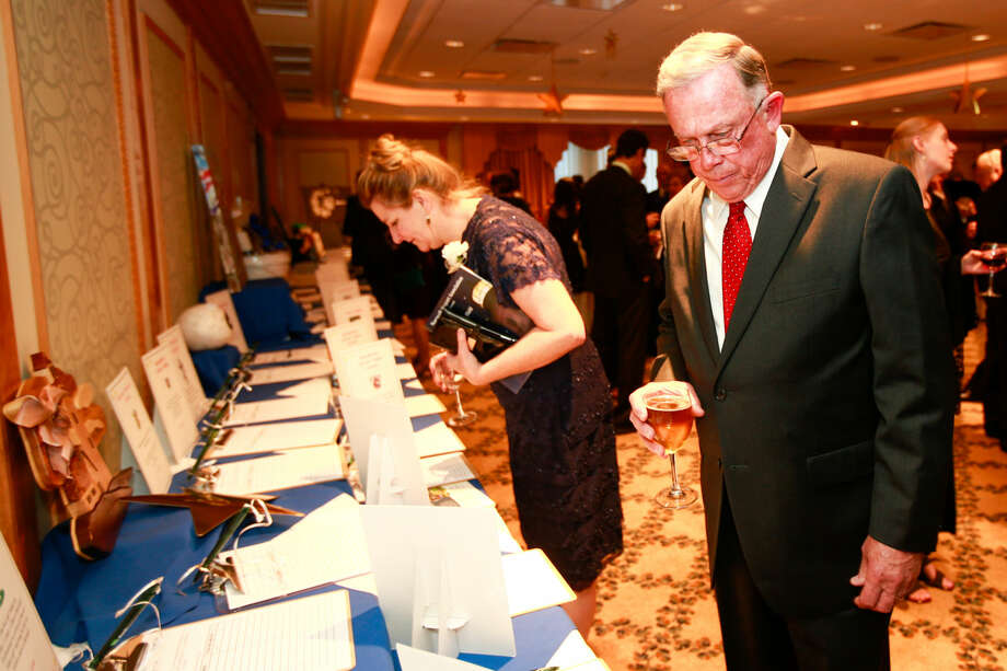 Hour photo/Chris Palermo. Former Seaport Association President Don Elleck looks at the silent auction items at the Norwalk Seaport Association annual Lightkeeper's Gala at the Norwalk Inn Saturday night.
