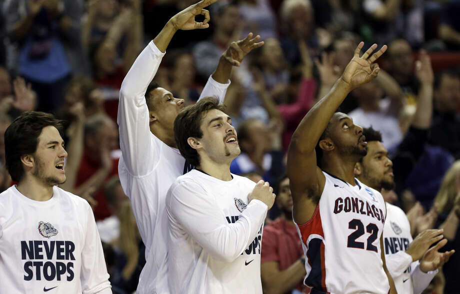 Players on Gonzaga's bench cheer a 3-point basket by the team against North Dakota State during the first half of an NCAA tournament college basketball game in the Round of 64 in Seattle, Friday, March 20, 2015. (AP Photo/Elaine Thompson)