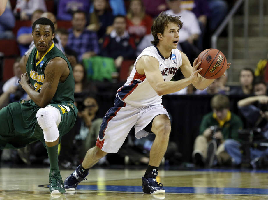 Gonzaga's Kevin Pangos, right, passes after he made a turn in front of North Dakota State's Kory Brown during the first half of an NCAA tournament college basketball game in the Round of 64 in Seattle, Friday, March 20, 2015. (AP Photo/Elaine Thompson)
