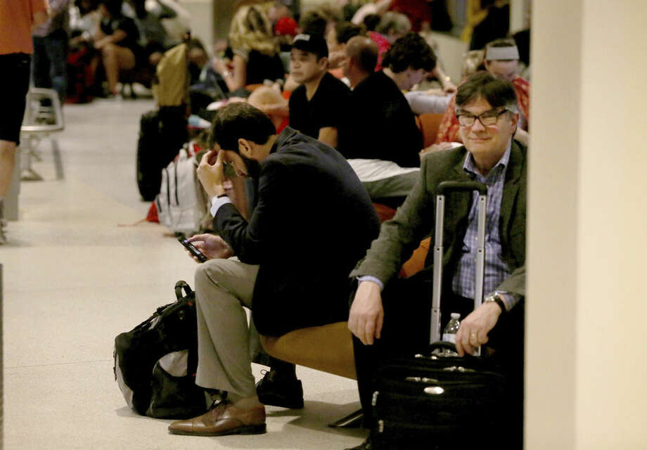 Fliers await word of their departures in the ticketing area of Louis Armstrong International Airport after a machete-wielding man was shot by a TSA employee on Concourse B on Friday, March 20, 2015. (AP Photo/NOLA.com The Times-Picayune, Michael DeMocker, Nola.com)