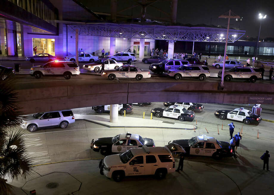 Dozens of police vehicles surround the entrance to New Orleans Louis Armstrong International Airport after a machete-wielding man was shot by a TSA employee in Concourse B on Friday, March 20, 2015. (AP Photo/NOLA.com The Times-Picayune, Michael DeMocker, Nola.com)