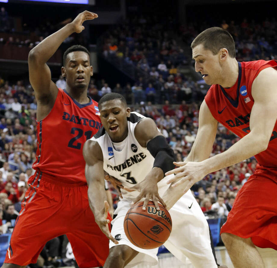 Providence's Kris Dunn (3) loses the ball against Dayton's Dyshawn Pierre, left, and Bobby Wehrli in the second half of an NCAA tournament college basketball game in the Round of 64 in Columbus, Ohio, Saturday, March 21, 2015. (AP Photo/Paul Vernon)