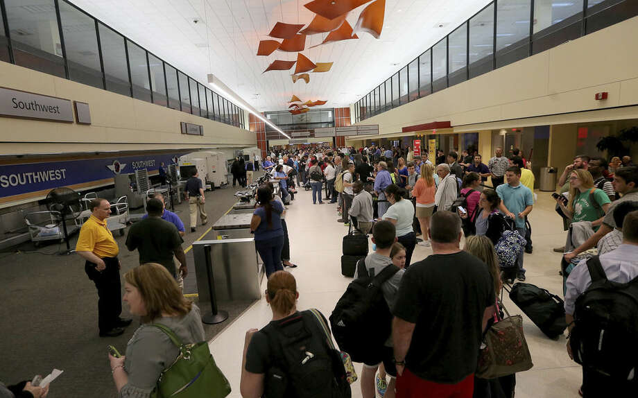 Long lines of fliers await word of their departures in the ticketing area of Louis Armstrong International Airport after a machete-wielding man was shot by a TSA employee on Concourse B on Friday, March 20, 2015. (AP Photo/NOLA.com The Times-Picayune, Michael DeMocker, Nola.com)