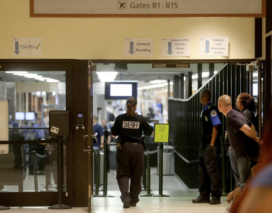 Police investigate on Concourse B of New Orleans Louis Armstrong International Airport after a machete-wielding man was shot by a TSA employee on Friday, March 20, 2015. (AP Photo/NOLA.com The Times-Picayune, Michael DeMocker, Nola.com)