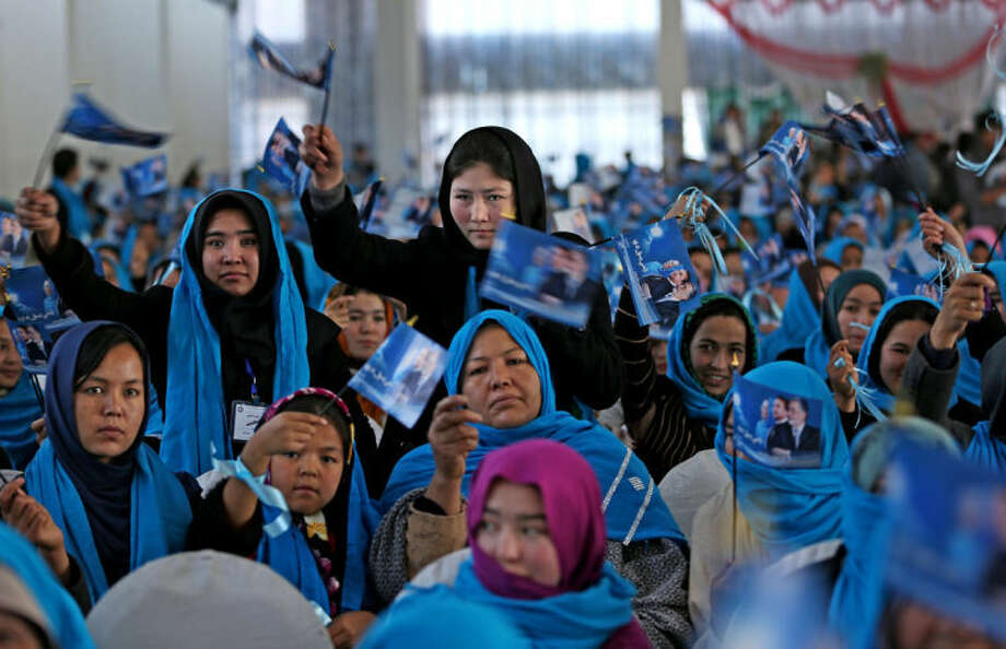 """In this photo taken on Monday, March 17, 2014, female supporters of Afghan vice presidential candidate, Habiba Sarabi and Afghan presidential candidate Zalmai Rassoul hold flags with his photo and two vice presidential candidate's during a campaign rally in Kabul, Afghanistan. The Afghan vice presidential candidate strode down the aisle separating hundreds of male and female supporters at a campaign rally in Kabul. She shook hands with the women filling the chairs to her right. To the men on the other side, she simply nodded. Writing on the flags reads, """"vote for Zalmai Rassoul."""" (AP Photo/Massoud Hossaini)"""
