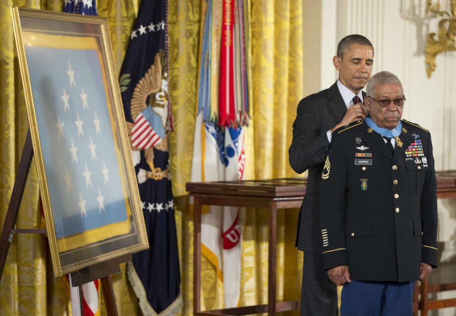 President Barack Obama awards Army Staff Sgt. Melvin Morris the Medal of Honor during a ceremony in the East Room of the White House in Washington, Tuesday, March 18, 2014. President Obama awarded the Medals of Honor to 24 ethnic or minority U.S. soldiers who performed acts of bravery under fire in three of the nation's wars, that were denied because of prejudice. (AP Photo/Manuel Balce Ceneta)