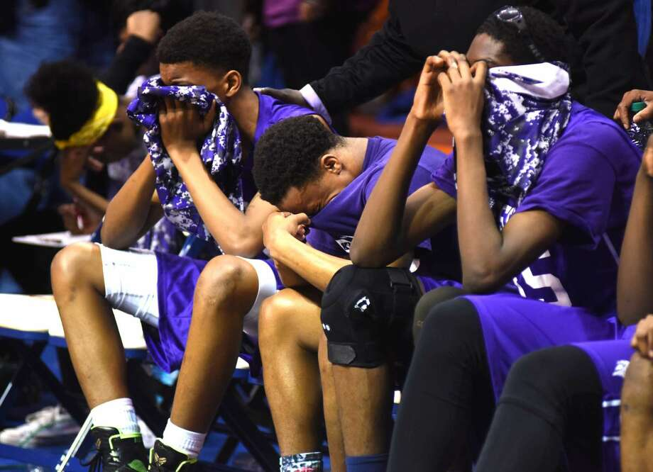 Hour photo/John Nash - Members of the Westhill High boys basketball team sit stunned after falling to Fairfield Prep in the Class LL boys basketball championship game at Mohegan Sun Arena on Saturday night.