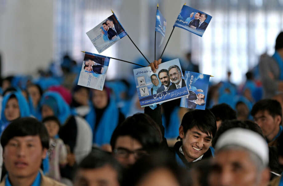 """In this photo taken on Monday, March 17, 2014, supporters of Afghan vice presidential candidate, Habiba Sarabi and Afghan presidential candidate Zalmai Rassoul hold flags with his photo and two vice presidential candidate's photos during a campaign rally in Kabul, Afghanistan. Sarabi, who already has been the first female governor in Afghanistan, is the most prominent woman running on a ticket in the April 5, 2014 election that will mark the first democratic transfer of power since the 2001 U.S.-led invasion that ousted the Taliban. But she still faces cultural norms in this deeply conservative Islamic society. The stadium where Sarabi gave her address was equally packed with men and women, although they sat on separate sides of the room. Writing on the flags reads, """"vote for Zalmai Rassoul."""" (AP Photo/Massoud Hossaini)"""