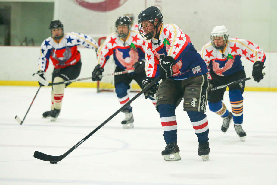 Hour photo/Chris Palermo. Norwalk Police Officer Garett Kruger slaps the puck up the ice as members of the Norwalk Police and Fire Departments face off at the Heritage Olympiad tournament at SoNo Ice House Saturday evening.