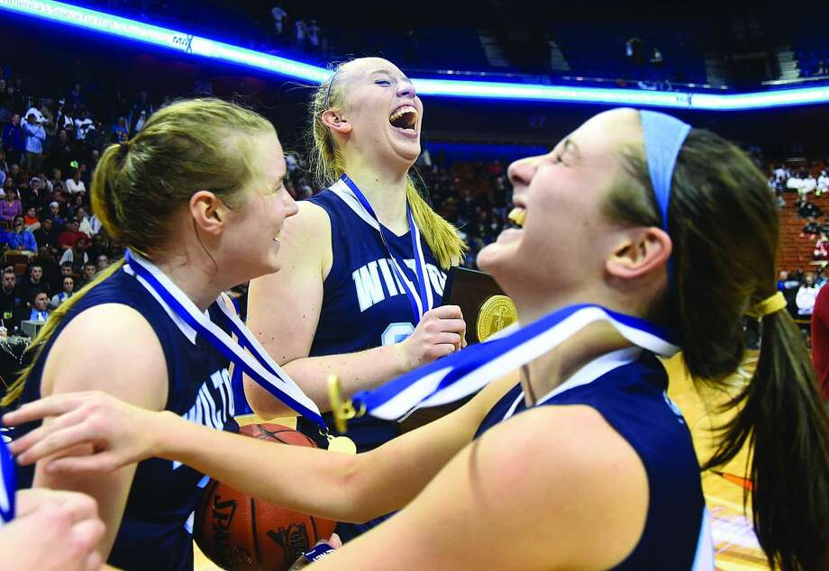 Hour photo/John Nash - Wilton High girls basketball players, from left, Erin Cunningham, Erica Meyer and Haley English celebrate their Class LL state championship win over South Windsor on Saturday at Mohegan Sun Arena. See Page B1.