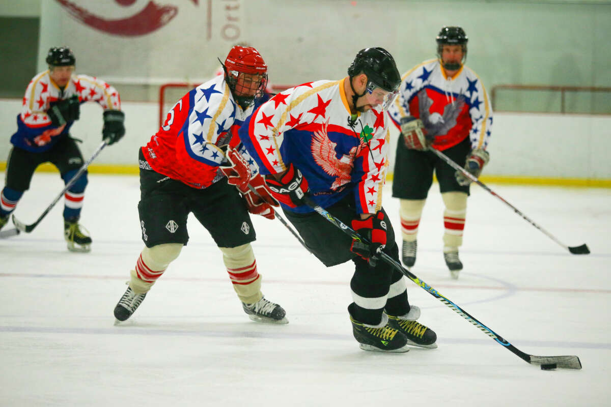 Hour photo/Chris Palermo. Norwalk Police Officer Jay Scanlan takes the pick up the rink as members of the Norwalk Police and Fire Departments face off at the Heritage Olympiad tournament at SoNo Ice House Saturday evening.
