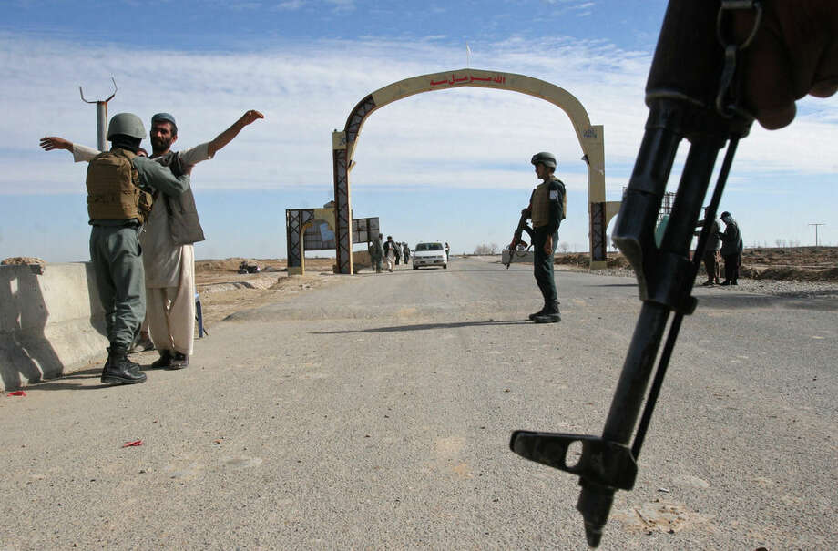 FILE - In this Feb. 26, 2015 file photo, Afghan security police stand guard at checkpoint in Helmand province, south of Kabul, Afghanistan. The Obama administration is suggesting it could reconsider its plan to remove nearly all U.S. troops from Afghanistan by the end of 2016 as part of an effort to ensure that the Afghans can maintain security in their country. (AP Photo/Abdul Khaliq, File)