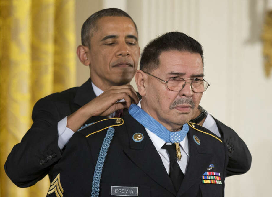 President Barack Obama awards Army Spc. Santiago Erevia the Medal of Honor during a ceremony in the East Room of the White House in Washington, Tuesday, March 18, 2014. President Obama awarded the Medals of Honor to 24 ethnic or minority U.S. soldiers who performed acts of bravery under fire in three of the nation's wars, that were denied because of prejudice. (AP Photo/Manuel Balce Ceneta)