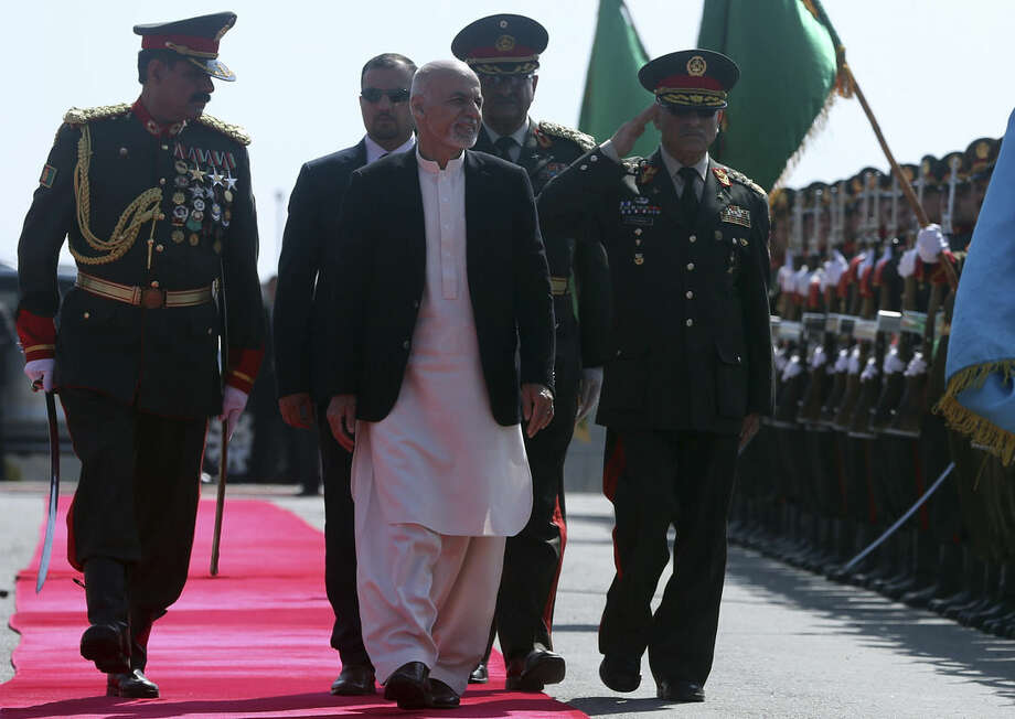 In this photo taken Wednesday, March 18, 2015, Afghanistan's President Ashraf Ghani, center, inspects the guard of honor during a graduation ceremony in a military academy in Kabul, Afghanistan. As Ghani heads to the United States on his first trip to Washington as head of state, the landmark visit offers a chance for both sides to start afresh and wipe the slate clean on the legacy of troubled U.S-Afghan relations. (AP Photo/Massoud Hossaini)