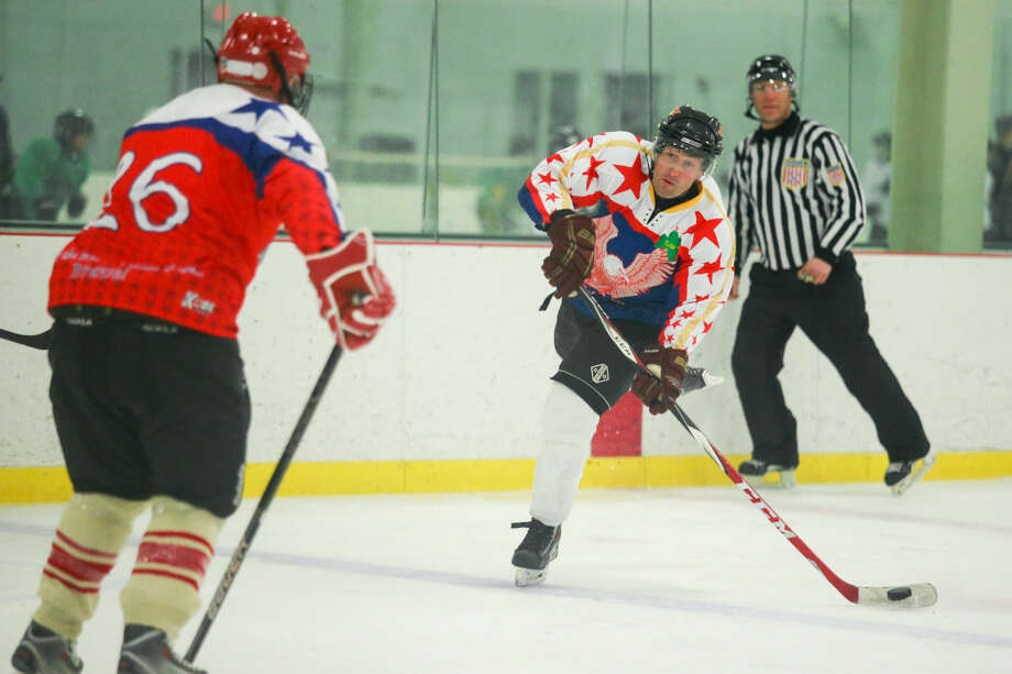 Hour photo/Chris Palermo. Norwalk Police Officer Louie Giannattasio passes the puck as members of the Norwalk Police and Fire Departments face off at the Heritage Olympiad tournament at SoNo Ice House Saturday evening.