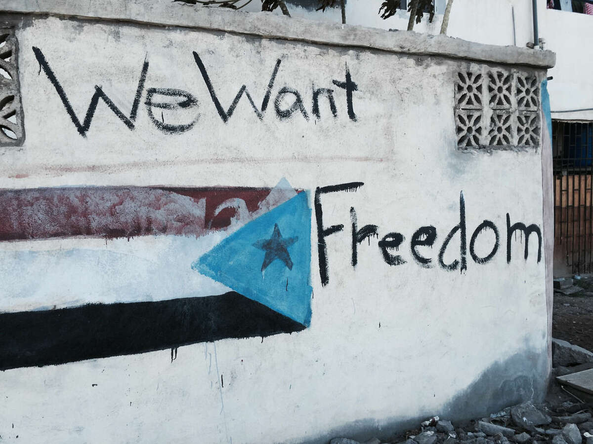 In this photo taken Saturday, March 21, 2015, graffiti depicting the old South Yemen flag that was used when southern Yemen was an independent state until 1990, covers the wall of a residence in Aden, Yemen. The city is visibly expecting assault, whether from the forces of Hadi's rival, ousted President Ali Abdullah Saleh, who has allied himself with the Shite rebels, or from al-Qaida militants. Army and police forces loyal to Hadi and their allied militiamen patrol Aden's streets and man checkpoints at key locations. Tanks guard roads leading to the city and children are largely staying home from school. (AP Photo/Hamza Hendawi)