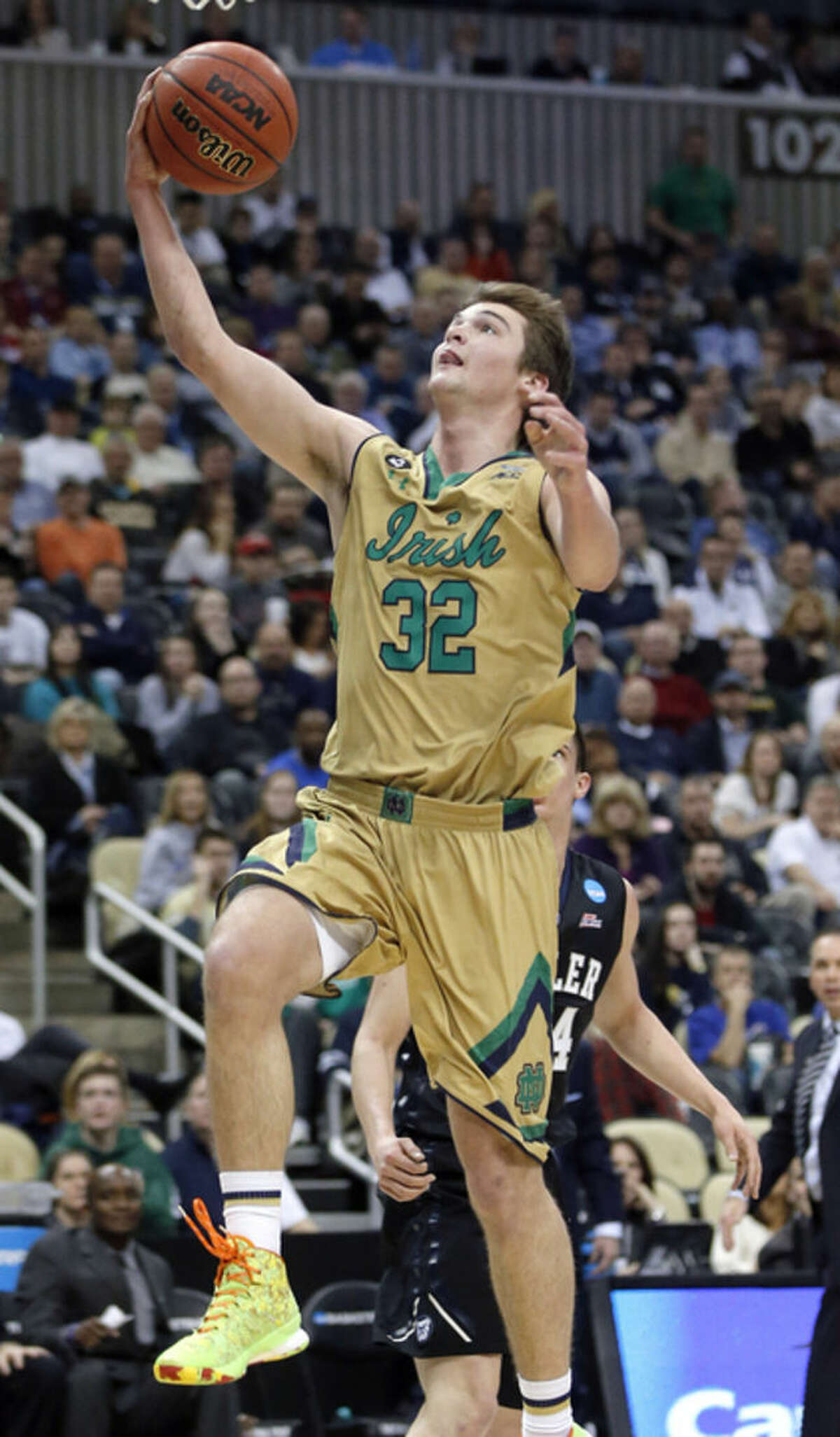 Notre Dame's Steve Vasturia (32) shoots in front of Butler's Kellen Dunham during the first half of an NCAA college basketball tournament Round of 32 game Saturday, March 21, 2015, in Pittsburgh. (AP Photo/Gene J. Puskar)