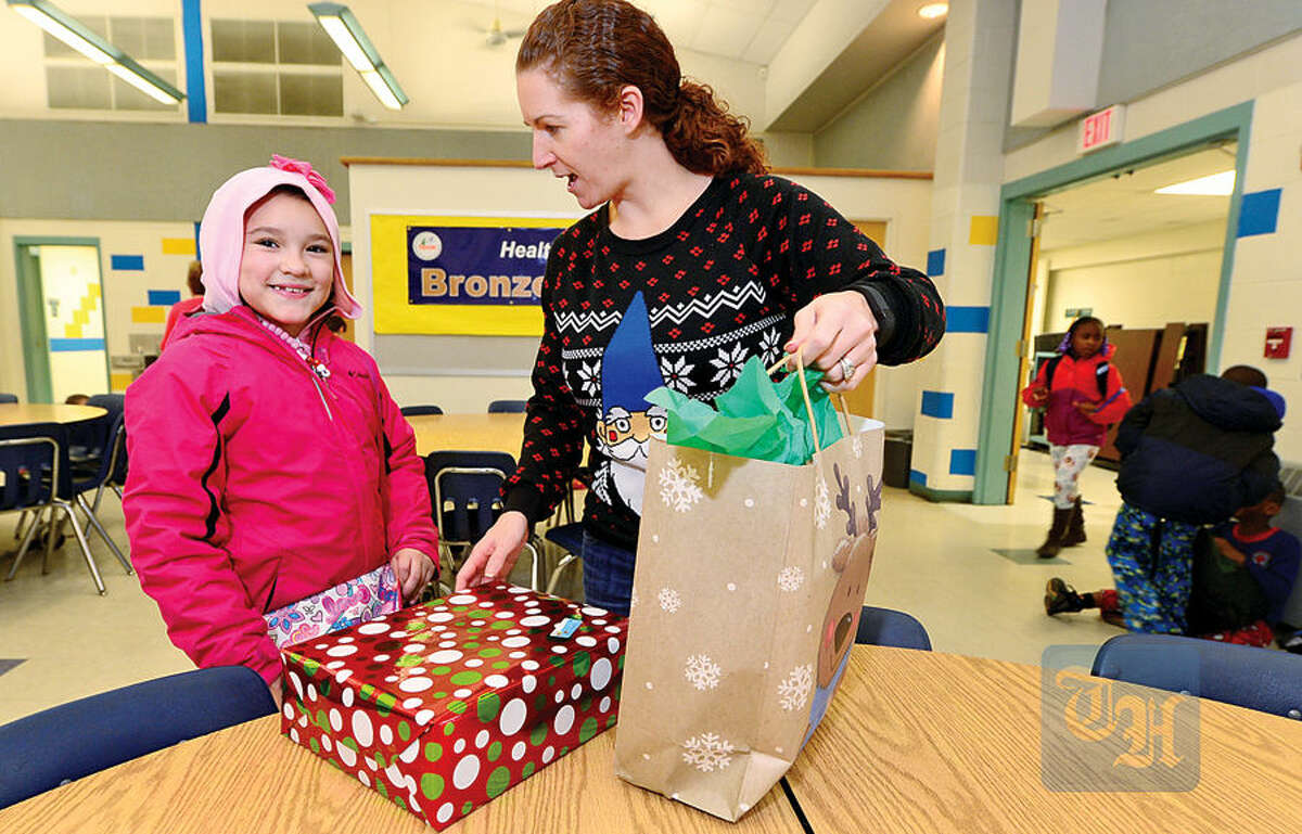Hour photo / Erik Trautmann In this file photo, students at Fox Run Elementary School including 3rd grader Saliyah Cordero receives a present from teacher Erin Bjernestad which was provided through the generosity of Walmart General Manager KelvinBernadine, who donated enough toys for nearly 100 needy students Wednesday.