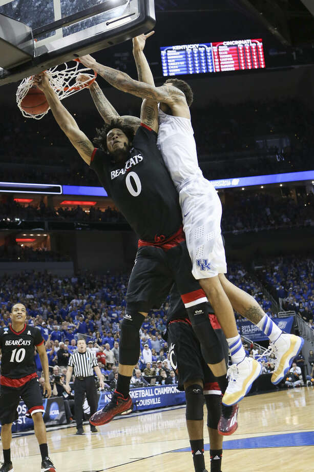 Kentucky forward Willie Cauley-Stein dunks over Cincinnati forward Quadri Moore during the first half of an NCAA tournament college basketball game in Louisville, Ky., Saturday, March 21, 2015. (AP Photo/David Stephenson)