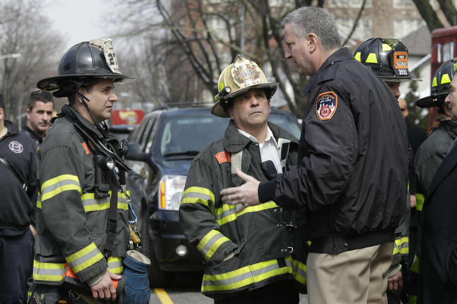 New York City Mayor Bill de Blasio, right, speaks to firefighters who responded to a fatal fire in the Brooklyn borough of New York, Saturday, March 21, 2015. The fire raged through the residence early Saturday, killing seven children and leaving two other people in critical condition, authorities said. (AP Photo/Mary Altaffer)