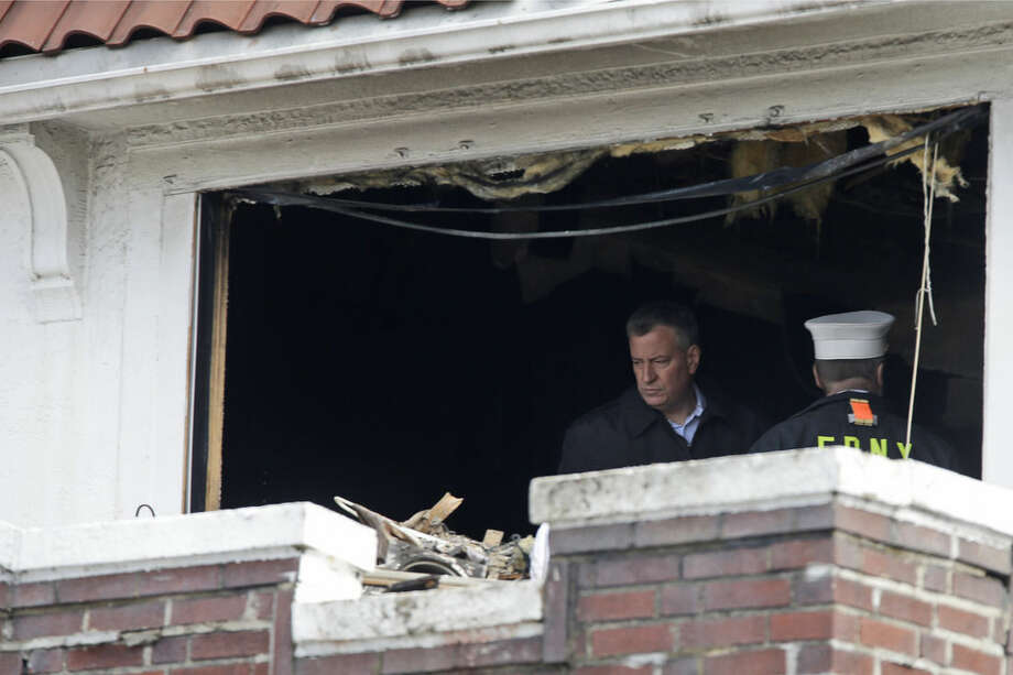New York City Mayor Bill de Blasio tours the scene of a fatal fire in the Brooklyn borough of New York, Saturday, March 21, 2015. The fire raged through the residence early Saturday, killing seven children and leaving two other people in critical condition, authorities said. (AP Photo/Mary Altaffer)