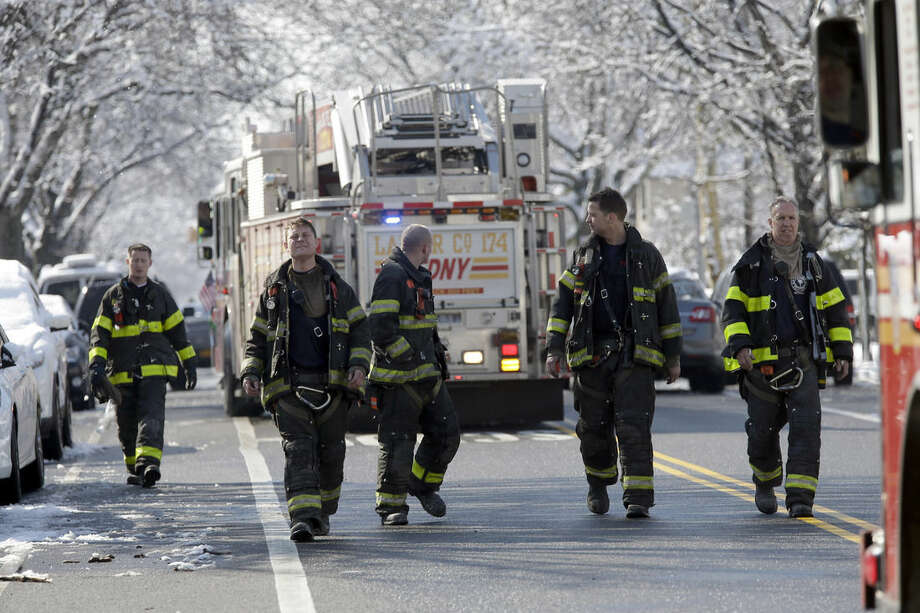 Firefighters leave the scene of an overnight fire in the Brooklyn borough of New York, Saturday, March 21, 2015. The fire raged through a residence early Saturday, killing seven children and leaving two other people in critical condition, authorities said. (AP Photo/Mary Altaffer)