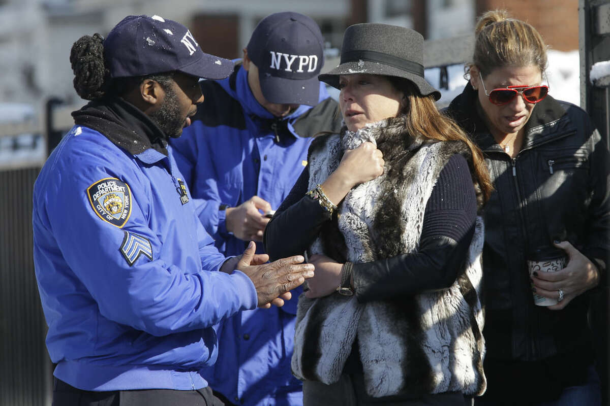 Community affairs police officers speak to women who say they are close friends of the family near the scene of an overnight fire in the Brooklyn borough of New York, Saturday, March 21, 2015. The fire raged through a residence early Saturday, killing seven children and leaving two other people in critical condition, authorities said. (AP Photo/Mary Altaffer)
