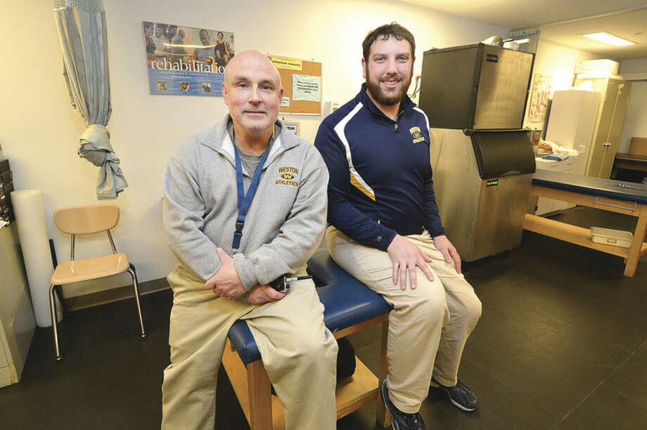 Hour photo/Alex von KleydorffWeston High School Athletic Trainers Dennis Richetelli, left, and Eric Peterson are in charge of taking care of the Trojans student-athletes when they're hurt while also helping to prevent them from being injured and nursing then back to health if they are out of action.