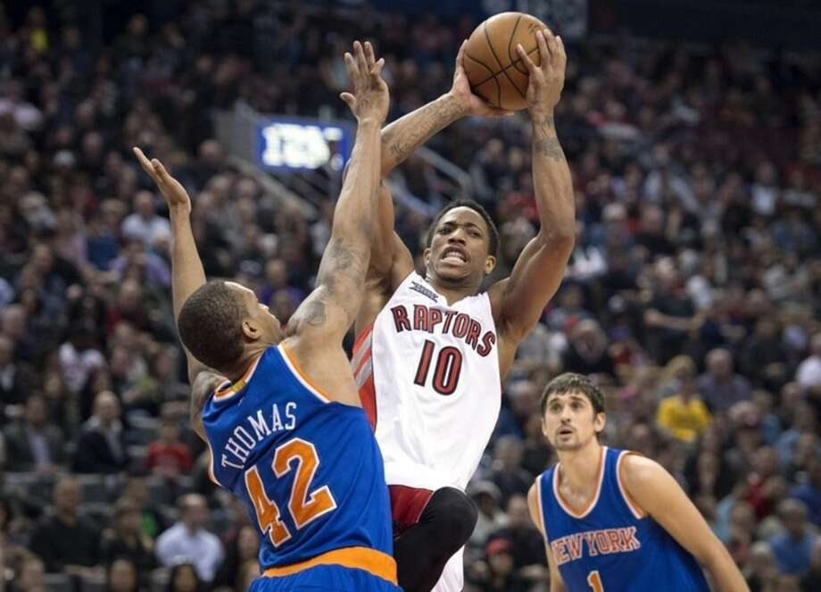 Toronto Raptors' DeMar DeRozan, center, looks to pass between New York Knicks Lance Thomas, left, and Alexey Shved during first-half NBA basketball game action in Toronto, Sunday, March 22, 2015. (AP Photo/The Canadian Press, Darren Calabrese)