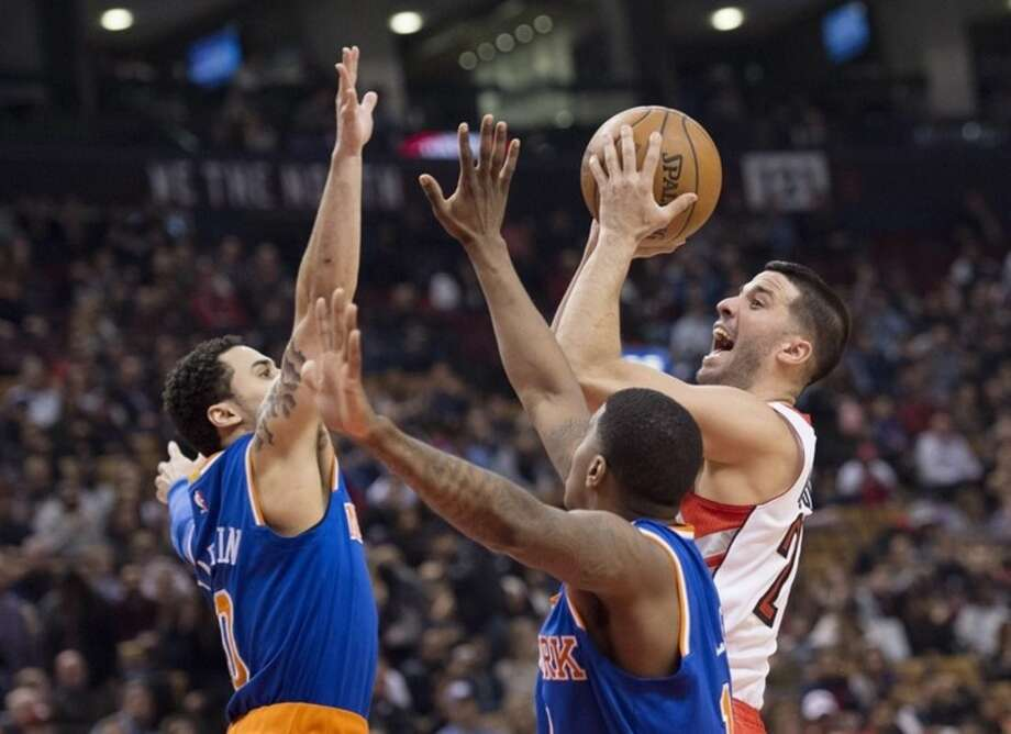 Toronto Raptors' Greivis Vasquez, right, shoots over New York Knicks' Shane Larkin, left, and Ricky Ledo during first-half NBA basketball game action in Toronto, Sunday, March 22, 2015. (AP Photo/The Canadian Press, Darren Calabrese)