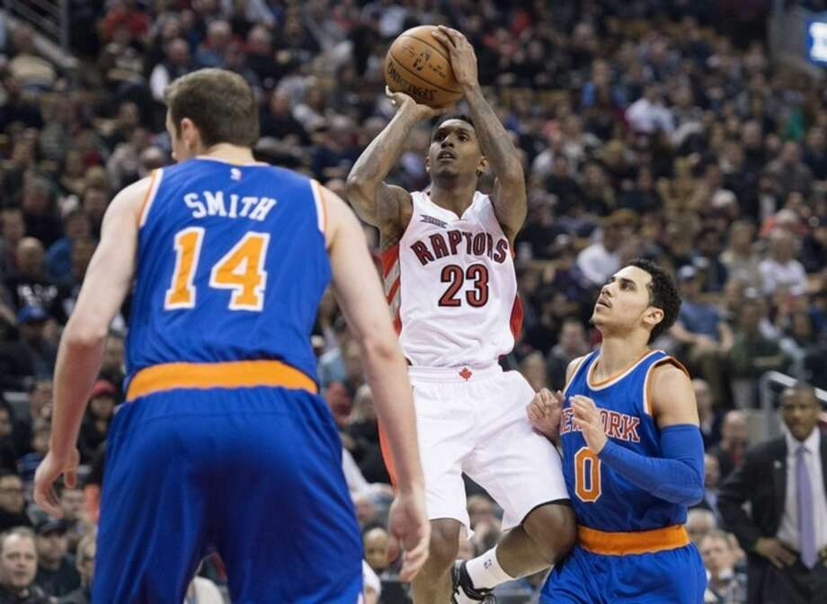 Toronto Raptors' Lou Williams, center, shoots between New York Knicks' Jason Smith, left, and Shane Larkin during first-half NBA basketball game action in Toronto, Sunday, March 22, 2015. (AP Photo/The Canadian Press, Darren Calabrese)