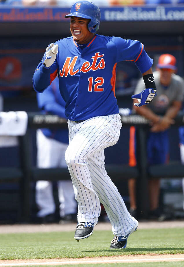 New York Mets' Juan Lagares (12) races home with an inside-the-park home run in the first inning of an exhibition spring training baseball game against the New York Yankees, Sunday, March 22, 2015, in Port St. Lucie, Fla. Yankees center fielder Jose Pirela was injured on the play. (AP Photo/John Bazemore)