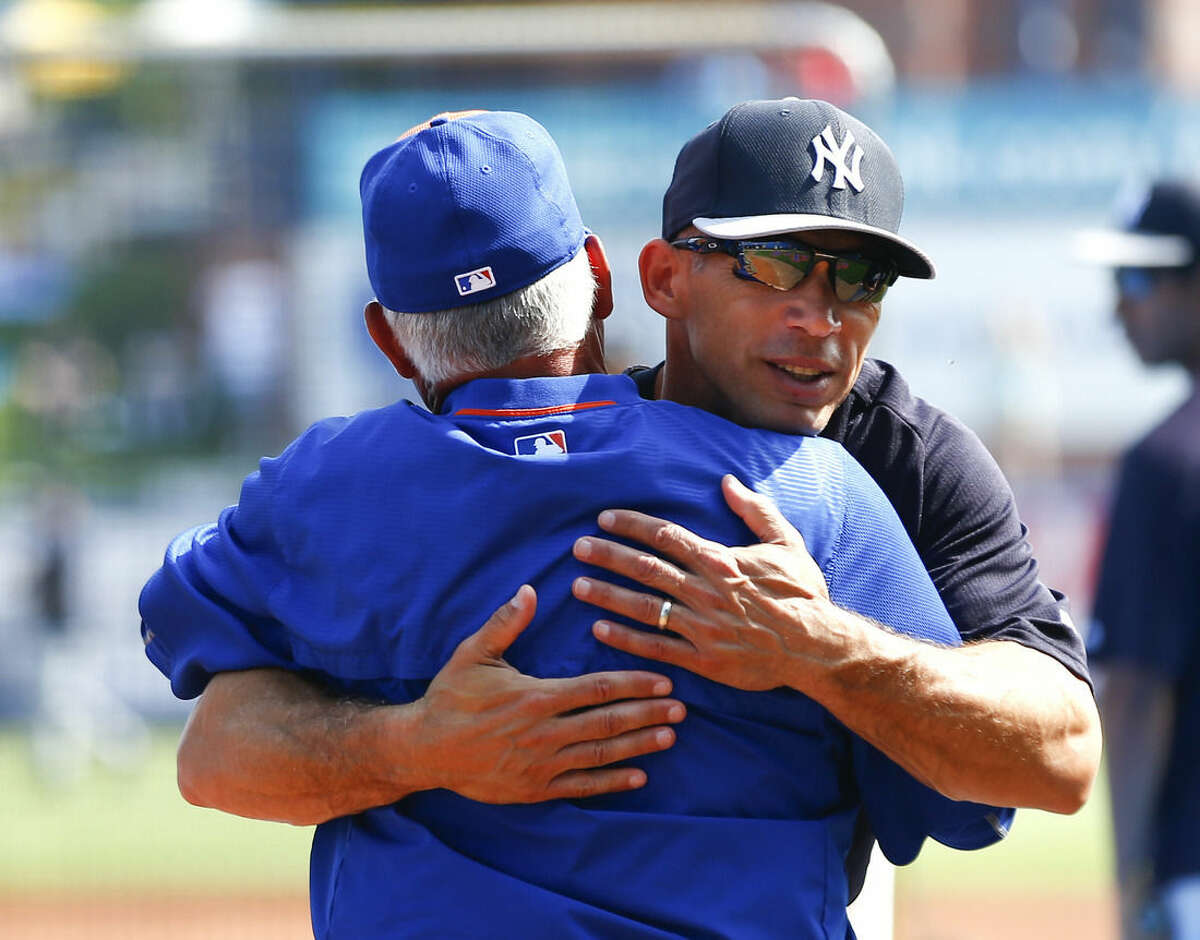 New York Yankees manager Joe Girardi, right, hugs, New York Mets manager Terry Collins at an exhibition spring training baseball game Sunday, March 22, 2015, in Port St. Lucie, Fla. (AP Photo/John Bazemore)