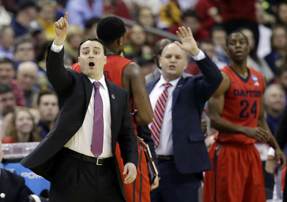 Dayton head coach Archie Miller, left, signals his team in the second half of an NCAA tournament college basketball game against Oklahoma in the Round of 32 in Columbus, Ohio, Sunday, March 22, 2015. (AP Photo/Tony Dejak)