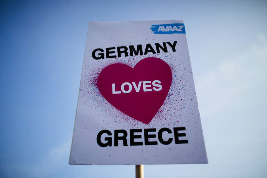 A protestor of the Avaaz organization holds up a poster during a demonstration for German-Greek solidarity prior to a bilateral meeting of German Chancellor Angela Merkel and the Prime Minister of Greece Alexis Tsipras at the chancellery in Berlin, Monday, March 23, 2015. (AP Photo/Markus Schreiber)